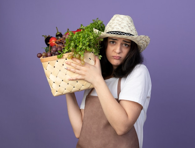 Enttäuschte junge brünette gärtnerin in uniform mit gartenhut hält gemüsekorb isoliert auf lila wand