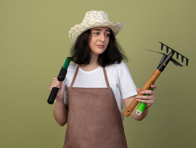 Enttäuschte junge brünette gärtnerin in uniform mit gartenhut hält und betrachtet gartengeräte isoliert auf olivgrüner wand