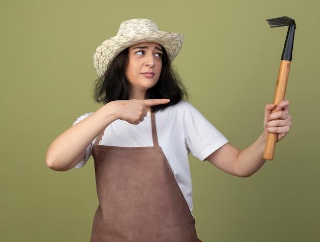 Enttäuschte junge brünette gärtnerin in uniform mit gartenhut hält und zeigt auf rechen isoliert auf olivgrüner wand