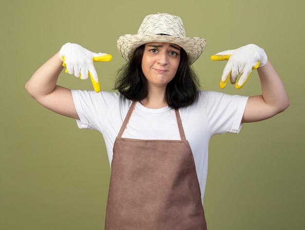 Enttäuschte junge brünette gärtnerin in uniform mit gartenhut und handschuhen zeigt mit zwei händen auf olivgrüne wand