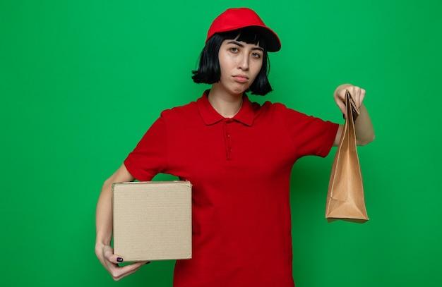 Enttäuschte junge kaukasische lieferfrau, die lebensmittelverpackungen und karton hält