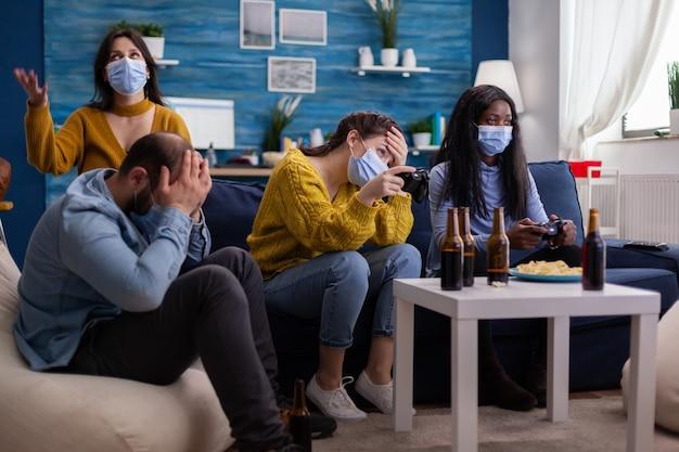 Enttäuschte menschen, die videospiele zu hause verlieren, weil sie die soziale distanzierung wegen des corona-ausbruchs mit gesichtsmaske gegen die verbreitung von viren respektieren. neue normale party soziale distanz
