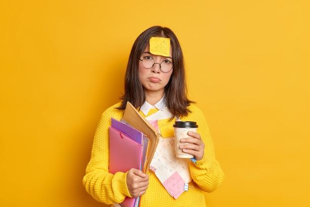 Enttäuschte müde absolventin bereitet sich auf die prüfungssitzung vor hat frist von haftnotizen umgeben und papiere hält einweg tasse kaffee hat unglücklichen unzufriedenen ausdruck steht drinnen