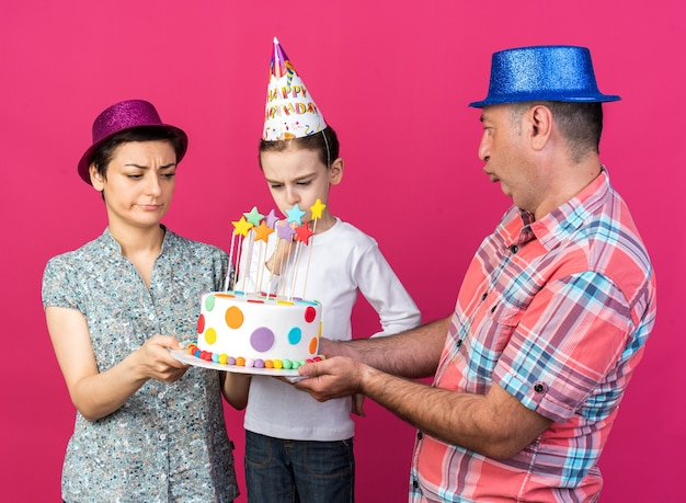 Enttäuschte mutter und vater mit partyhüten, die geburtstagskuchen zusammenhalten und ihren unzufriedenen sohn einzeln auf rosa wand mit kopienraum betrachten