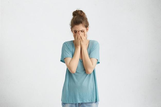 Enttäuschte, niedergeschlagene frau mit haarknoten, die ein blaues, lockeres t-shirt trägt, das ihr gesicht mit müden und erschöpften händen bedeckt. verzweifelte frau, die depression hat, die ihr weinendes gesicht mit den händen versteckt