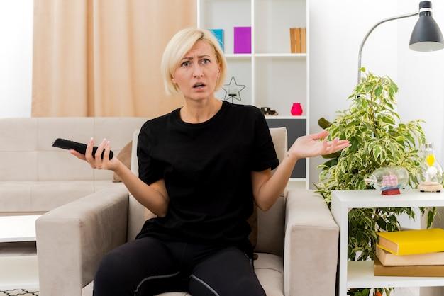 Enttäuschte schöne blonde russische frau sitzt auf sessel, der tv-fernbedienung hält, die seite innerhalb des wohnzimmers schaut