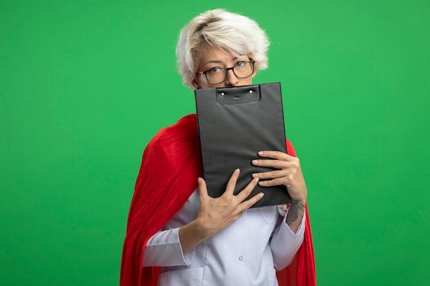 Enttäuschte slawische superheldenfrau in arztuniform mit rotem umhang und stethoskop in optischen gläsern hält zwischenablage isoliert auf grüner wand mit kopierraum