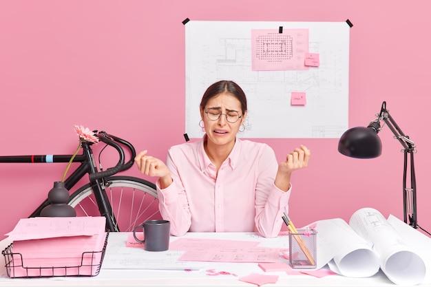Enttäuschte, traurige büroangestellte, die das gefühl hat, dass die verzweiflung die arbeit an neuen bauprojekten, umgeben von papieren am desktop, nicht beenden kann