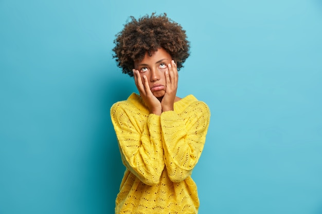 Enttäuschte traurige müdigkeit frau berührt wangen und sieht gelangweilt fühlt sich unglücklich nach prüfungsversagen in gelben pullover posen gegen blaue wand posiert