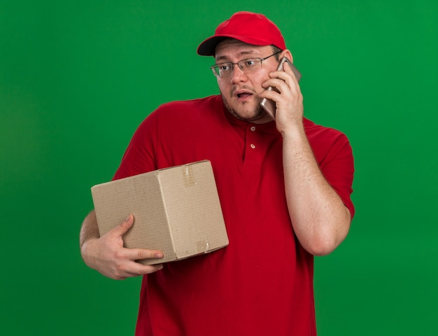 Enttäuschte übergewichtige junge lieferbote in optischen gläsern, die pappkarton halten und am telefon lokalisiert auf grüner wand mit kopierraum sprechen Kostenlose Fotos