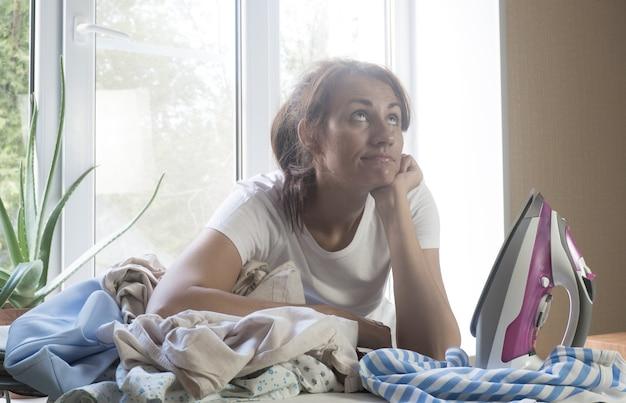 Enttäuschte unglückliche hausfrau, die sich auf einen wäschehaufen auf dem bügelbrett stützt