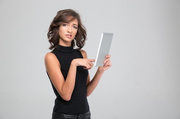 Enttäuschte verärgerte junge frau in schwarzer kleidung mit tablet