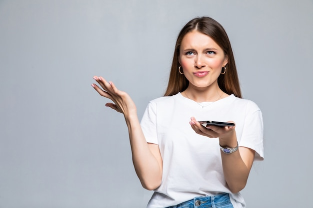 Enttäuschte verwirrte frau mit smartphone isoliert