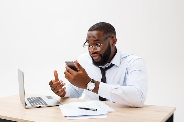 Enttäuschter afrikanischer geschäftsmann wird betäubt und verwirrt, am telefon sprechend.