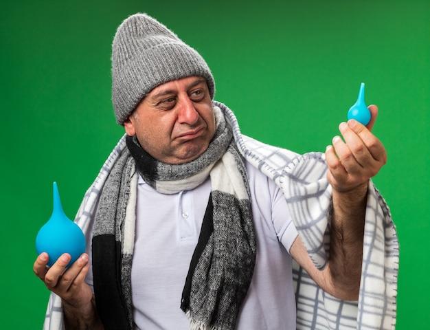 Enttäuschter erwachsener kranker kaukasischer mann mit schal um den hals, der eine wintermütze trägt, die in kariertes halten gewickelt ist und einläufe einzeln auf grüner wand mit kopienraum betrachtet