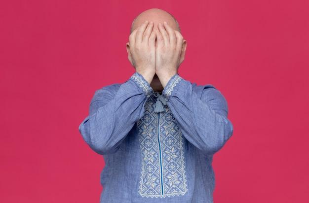 Enttäuschter erwachsener mann im blauen hemd mit brille, der sich die hände aufs gesicht legt