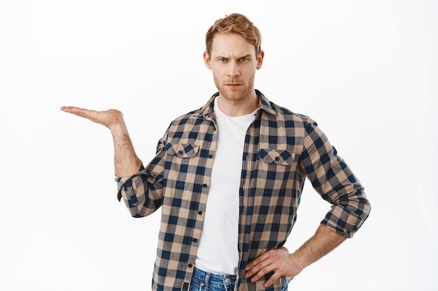 Enttäuschter erwachsener mann mit roten haaren, der einen gegenstand in der offenen hand hält, verurteilend aussieht, einen gegenstand in seiner handfläche zeigt und über weißer wand steht