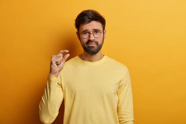 Enttäuschter erwachsener mann zeigt geringe größe, misst etwas sehr winziges mit den fingern, zeigt unzureichende länge oder dicke, diskutiert sinkende preise, in freizeitkleidung gekleidet, posiert drinnen