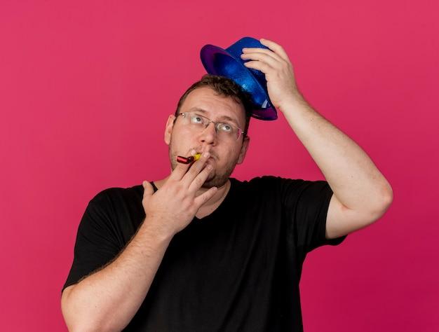 Enttäuschter erwachsener slawischer mann in optischer brille, der einen blauen partyhut über dem kopf hält und eine partypfeife bläst