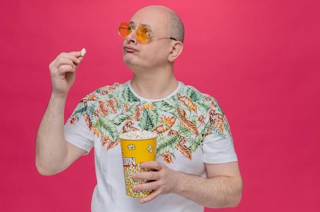 Enttäuschter erwachsener slawischer mann mit sonnenbrille, der popcorn-eimer hält und aufschaut