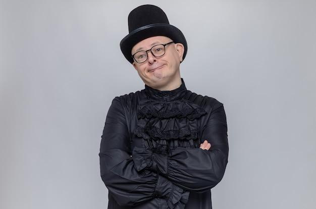 Enttäuschter erwachsener slawischer mann mit zylinder und optischer brille in schwarzem gothic-hemd, der mit verschränkten armen steht