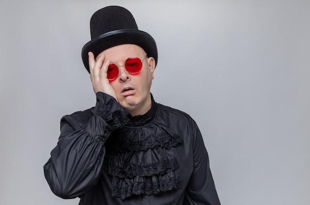 Enttäuschter erwachsener slawischer mann mit zylinder und sonnenbrille in schwarzem gothic-hemd, der die hand auf sein gesicht legt und