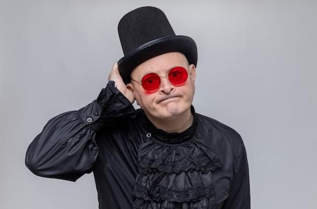 Enttäuschter erwachsener slawischer mann mit zylinder und sonnenbrille in schwarzem gothic-hemd mit blick auf die vorderseite