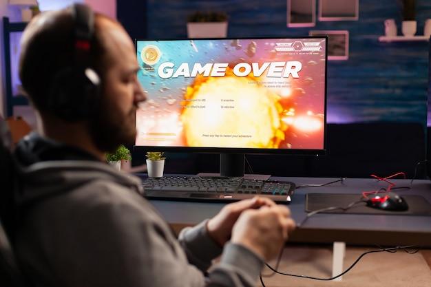 Enttäuschter esport-spieler, der ein virtuelles turnier-videospiel mit einem drahtlosen controller verliert. besiegter mann, der einen online-weltraum-shooter-wettbewerb mit einem leistungsstarken professionellen computer mit joystick spielt