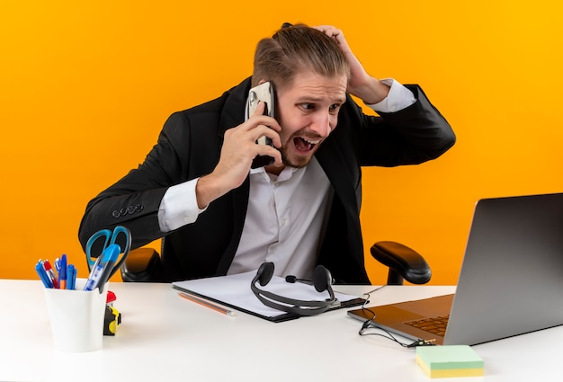 Enttäuschter gutaussehender geschäftsmann im anzug, der am laptop arbeitet, der auf handy spricht, verwirrt und unzufrieden am tisch in offise über orange hintergrund sitzt