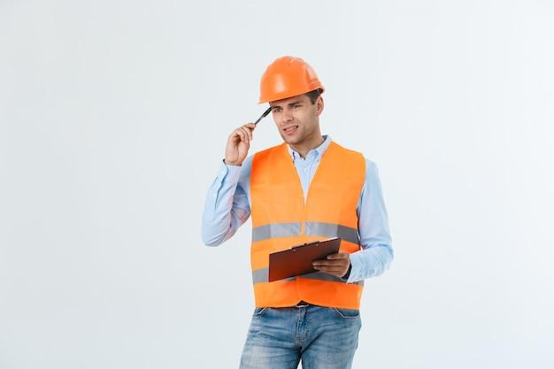 Enttäuschter, gutaussehender ingenieur mit orangefarbener weste und jeans mit helm, isoliert auf weißem hintergrund.