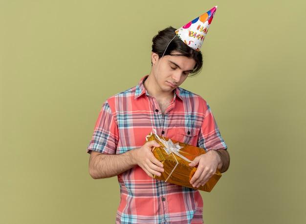 Enttäuschter gutaussehender kaukasischer mann mit geburtstagsmütze steht mit geschlossenen augen und hält geschenkbox