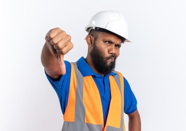 Enttäuschter junger afroamerikanischer baumeister in uniform mit schutzhelm, der isoliert auf weißem hintergrund mit kopienraum herunterfällt