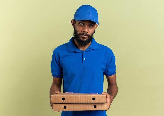 Enttäuschter junger afroamerikanischer lieferer, der pizzakartons isoliert auf olivgrüner wand mit kopierraum hält