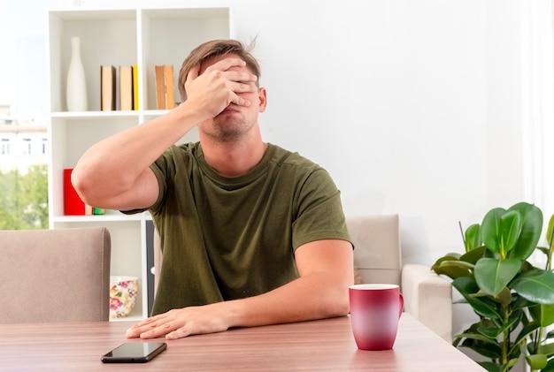 Enttäuschter junger blonder gutaussehender mann sitzt am tisch mit tasse und telefon, die hand auf gesicht schließend augen im wohnzimmer schließend
