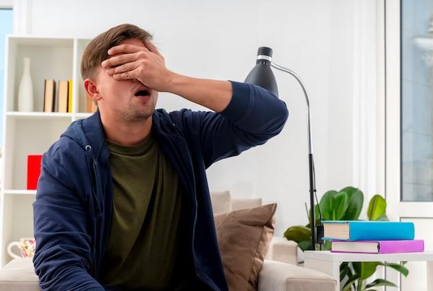 Enttäuschter junger blonder gutaussehender mann sitzt auf sessel und legt hand auf gesicht, das auge im wohnzimmer schließt