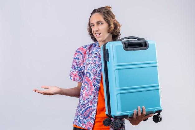 Enttäuschter junger hübscher reisender kerl, der koffer hält, der mit verwirrendem gesichtsausdruck steht stehend