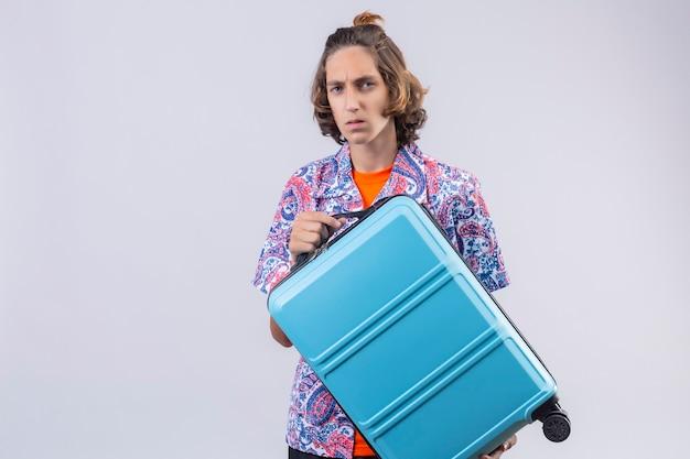 Enttäuschter junger hübscher reisender kerl, der koffer mit stirnrunzelndem gesicht stehend hält