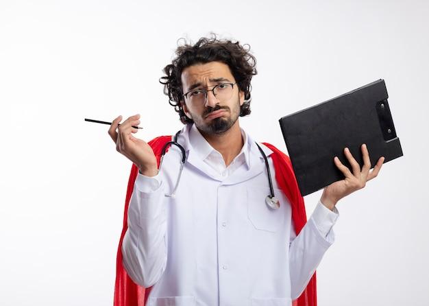 Enttäuschter junger kaukasischer superheldenmann in der optischen brille, die arztuniform mit rotem umhang und mit stethoskop um hals trägt, hält bleistift und zwischenablage mit kopierraum