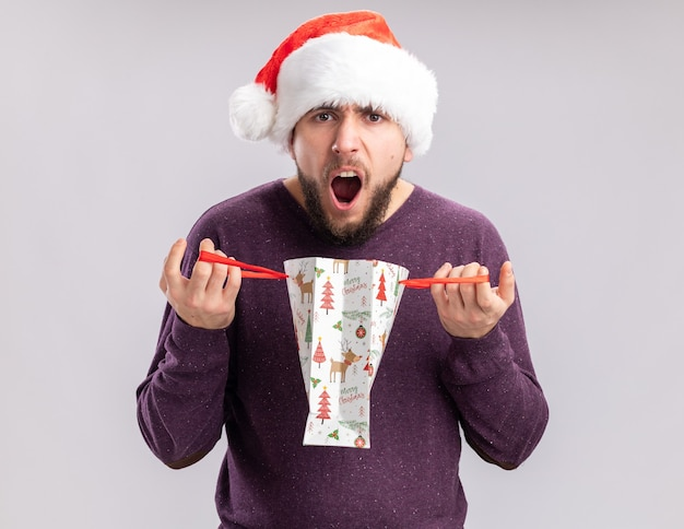 Enttäuschter junger mann in lila pullover und weihnachtsmütze, der eine geschenkpapiertüte öffnet, die mit aggressivem ausdruck auf weißem hintergrund schreit