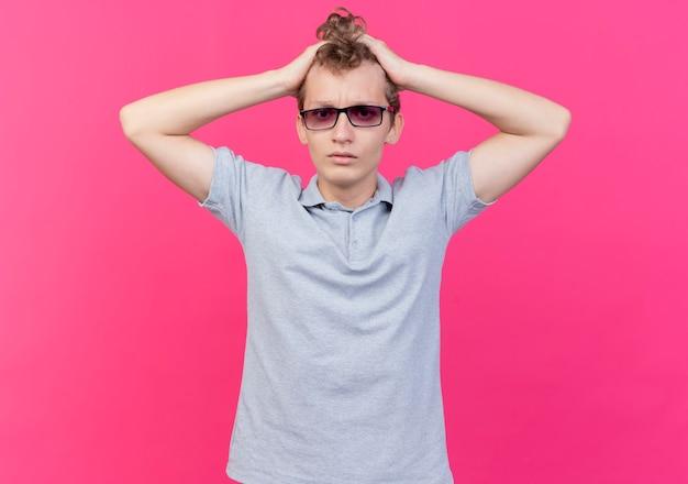 Enttäuschter junger mann in schwarzer brille, der graues poloshirt trägt, das seinen kopf berührt, der verwirrt ist, der über rosa wand steht