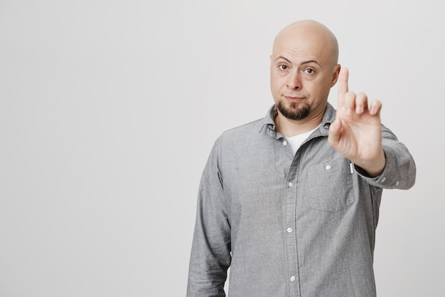 Enttäuschter kahler mann mittleren alters, der finger schüttelt, schimpft oder verbietet