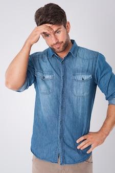 Enttäuschter mann, der ein jeanshemd trägt