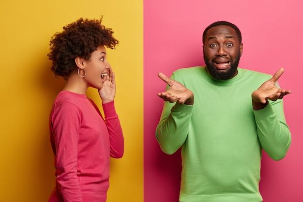 Enttäuschter schwarzer mann breitet handflächen aus, sieht zögernd und unglücklich aus, steht vor einer problematischen situation, positive afroamerikanische frau flüstert dem freund ein geheimnis zu, steht seitwärts. rosa und gelbe farbe