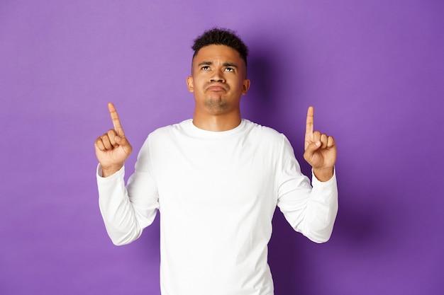 Enttäuschter und trauriger afroamerikaner junger mann im weißen sweatshirt, schauend und finger nach oben zeigend