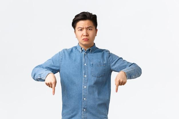 Enttäuschter und verärgerter junger asiate, der sich beschwert, besorgt und unzufrieden aussieht. mann im blauen hemd zeigt mit den fingern nach unten, macht eine ankündigung, macht auf beunruhigende nachrichten aufmerksam.