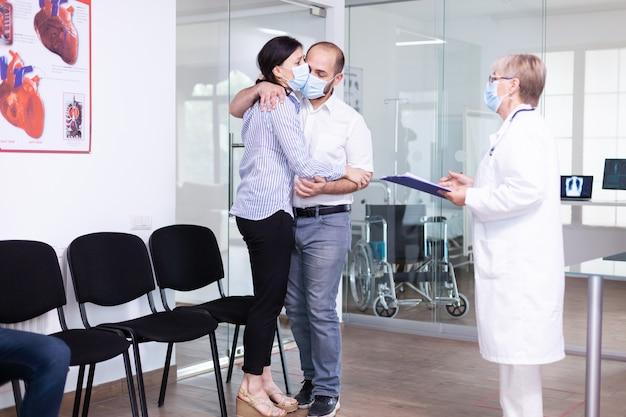 Enttäuschtes junges paar im wartebereich des krankenhauses vom arzt ungünstige schlechte nachrichten während des ausbruchs des coronavirus