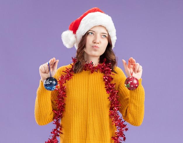 Enttäuschtes junges slawisches mädchen mit weihnachtsmütze und mit girlande um den hals, die glaskugelverzierungen hält, die auf der seite isoliert auf lila wand mit kopierraum schauen looking