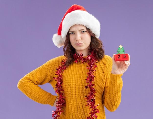 Enttäuschtes junges slawisches mädchen mit weihnachtsmütze und mit girlande um hals, die weihnachtsbaumverzierung lokalisiert auf lila hintergrund mit kopienraum hält
