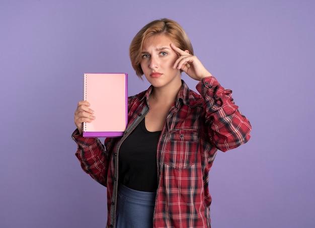 Enttäuschtes junges slawisches studentenmädchen legt hand auf tempel hält buch und notizbuch