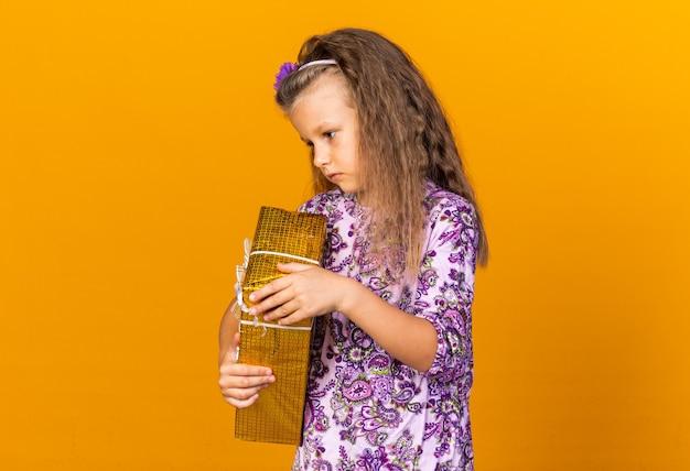 Enttäuschtes kleines blondes mädchen, das geschenkbox hält und die seite isoliert auf oranger wand mit kopierraum betrachtet